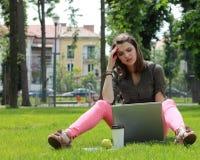 Mujer joven con el ordenador portátil Fotos de archivo libres de regalías