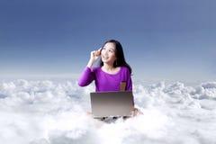 Mujer joven con el ordenador portátil debajo del cielo azul Fotografía de archivo