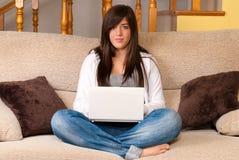 Mujer joven con el ordenador portátil del ordenador portátil que se sienta en el sofá Imagenes de archivo