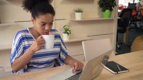 Mujer joven con el ordenador portátil dentro metrajes
