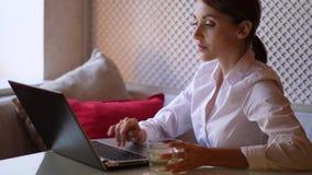 Mujer joven con el ordenador portátil en café metrajes