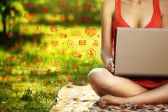 Mujer joven con el ordenador portátil en el parque de la hierba verde, infographic Foto de archivo