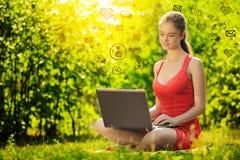 Mujer joven con el ordenador portátil en el parque de la hierba verde, infographic Imágenes de archivo libres de regalías