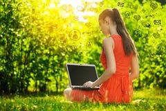Mujer joven con el ordenador portátil en el parque de la hierba verde, infographic Fotos de archivo