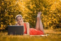 Mujer joven con el ordenador portátil en el parque en hierba, en otoño Fotos de archivo