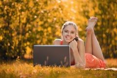 Mujer joven con el ordenador portátil en el parque en hierba, en otoño Fotografía de archivo libre de regalías