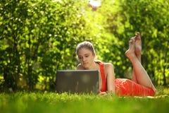 Mujer joven con el ordenador portátil en hierba verde en el parque Fotos de archivo
