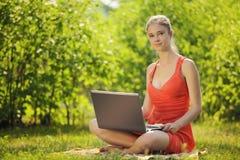 Mujer joven con el ordenador portátil en hierba verde en el parque Fotografía de archivo libre de regalías