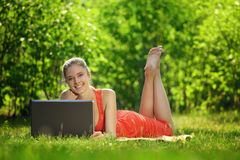 Mujer joven con el ordenador portátil en hierba verde en el parque Imagen de archivo libre de regalías