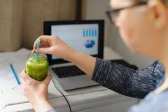 Mujer joven con el ordenador portátil en la tabla de madera Smoothie verde de consumición Fotografía de archivo libre de regalías