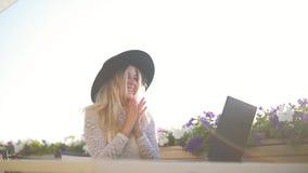Mujer joven con el ordenador portátil que se sienta en café cerca del mar, y trabajo almacen de video