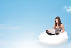 Mujer joven con el ordenador portátil que se sienta en la nube con el espacio de la copia Imágenes de archivo libres de regalías