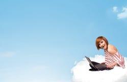 Mujer joven con el ordenador portátil que se sienta en la nube con el espacio de la copia Imagen de archivo libre de regalías
