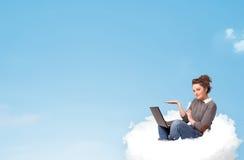 Mujer joven con el ordenador portátil que se sienta en la nube con el espacio de la copia Fotografía de archivo libre de regalías
