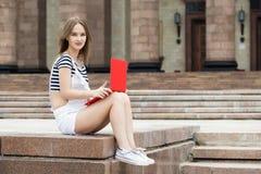 Mujer joven con el ordenador portátil que se sienta en las escaleras cerca de la universidad Fotografía de archivo