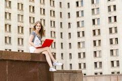 Mujer joven con el ordenador portátil que se sienta en las escaleras cerca de la universidad Imagen de archivo