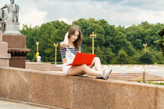 Mujer joven con el ordenador portátil que se sienta en las escaleras cerca de la universidad Foto de archivo libre de regalías