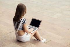 Mujer joven con el ordenador portátil que se sienta en las escaleras cerca de la universidad Imágenes de archivo libres de regalías