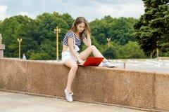 Mujer joven con el ordenador portátil que se sienta en las escaleras cerca de la universidad Fotografía de archivo libre de regalías