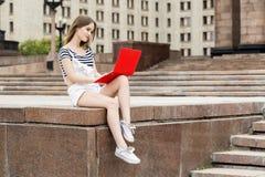 Mujer joven con el ordenador portátil que se sienta en las escaleras cerca de la universidad Fotos de archivo libres de regalías