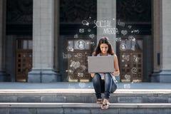Mujer joven con el ordenador portátil que se sienta en las escaleras, cerca de universidad Fotografía de archivo