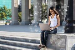 Mujer joven con el ordenador portátil que se sienta en las escaleras, cerca de universidad Fotografía de archivo libre de regalías