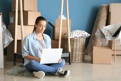 Mujer joven con el ordenador portátil que se sienta en piso cerca de las cajas y de las pertenencia dentro El trasladarse a nueva fotos de archivo libres de regalías