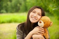 Mujer joven con el oso de peluche Fotos de archivo