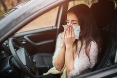 Mujer joven con el pañuelo La muchacha enferma tiene mocos el modelo femenino hace una curación para el frío común en el coche Foto de archivo
