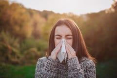 Mujer joven con el pañuelo La muchacha enferma tiene mocos El modelo femenino hace una curación para el frío común en un otoño Foto de archivo