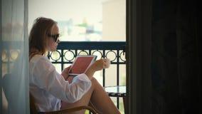 Mujer joven con el panel táctil en balcón del hotel almacen de video