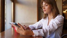 Mujer joven con el panel táctil en café almacen de metraje de vídeo