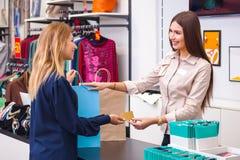 Mujer joven con el panier que da a su tarjeta de crédito al vendedor i Imagenes de archivo