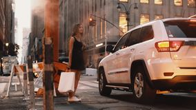 Mujer joven con el panier que se coloca cerca del centro de la ciudad del tubo del humo adentro de Nueva York, América cerca del  almacen de video