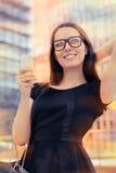 Mujer joven con el panier y Phone Out en la ciudad Foto de archivo