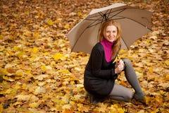 Mujer joven con el paraguas con las hojas de otoño imagen de archivo libre de regalías