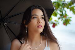 Mujer joven con el paraguas en día lluvioso por la playa Imagen de archivo