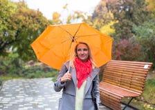 Mujer joven con el paraguas en parque hermoso del otoño fotos de archivo