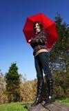 Mujer joven con el paraguas rojo Foto de archivo