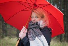 Mujer joven con el paraguas rojo en un día de inviernos lluviosos en un arbolado Imagen de archivo libre de regalías