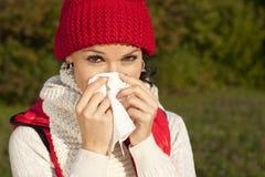 Mujer joven con el pañuelo y la gripe Fotografía de archivo libre de regalías