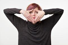 Mujer joven con el peinado colorido interesante que oculta su cara con la mano Imágenes de archivo libres de regalías