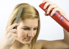 Mujer joven con el peine y la laca de pelo del rodillo Imagenes de archivo