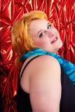 Mujer joven con el pelo de oro, exponiendo su hombro que da vuelta a la mano completa de la audiencia vestida en vestido del negro Fotos de archivo