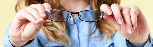 Mujer joven con el pelo del jengibre que sostiene los vidrios de lectura delante de ella Mujer joven con las gafas en fondo amari Fotos de archivo