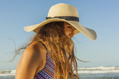 Mujer joven con el pelo largo en el sombrero del verano de la playa que lleva Fotos de archivo libres de regalías