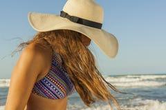 Mujer joven con el pelo largo en el sombrero del verano de la playa que lleva Fotografía de archivo