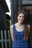 Mujer joven con el pelo largo en el fondo del granero de madera en el pueblo Imagen de archivo