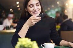 Mujer joven con el pelo largo que hace la foto por el smartphone de la taza de café, teniendo resto en café cerca de ventana Fotos de archivo libres de regalías