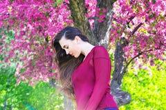 Mujer joven con el pelo largo que mira abajo delante de Sakura Fotos de archivo